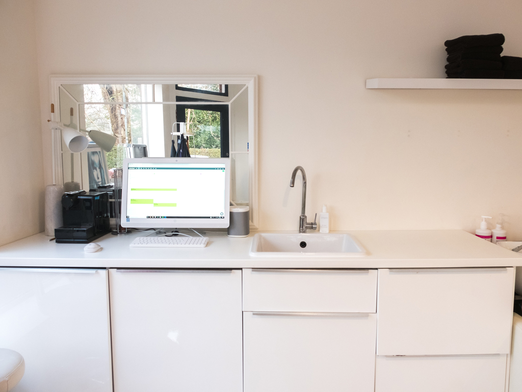View of the reception desk, alongside cupboards and a sink, within Ralph and Sydney Hair Salon.