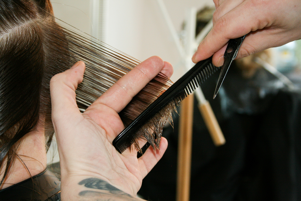 Glenn from Ralph and Sydney Hair Salon, combing a customer's hair with a comb