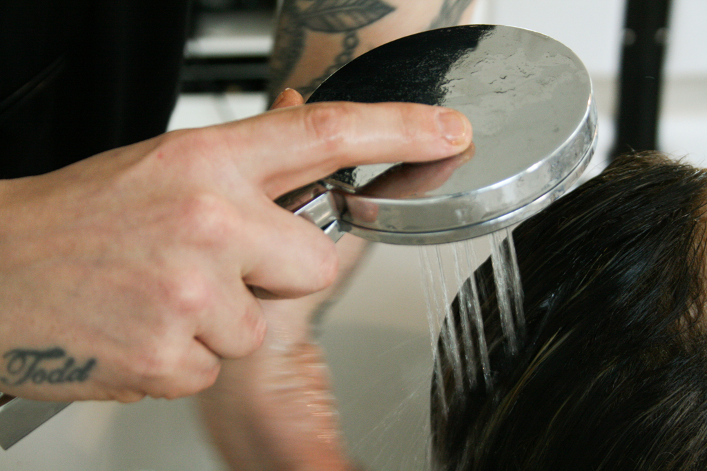 Glenn from Ralph and Sydney Hair Salon, washing a customer's hair with a shower head