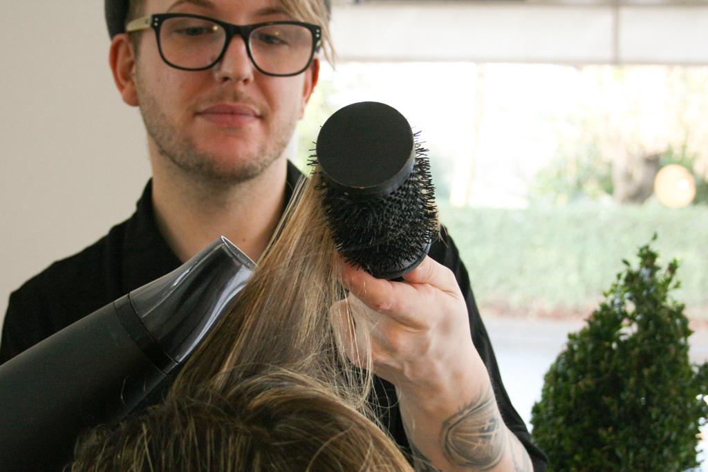 Glenn from Ralph and Sydney Hair Salon, dressing someone's hair.